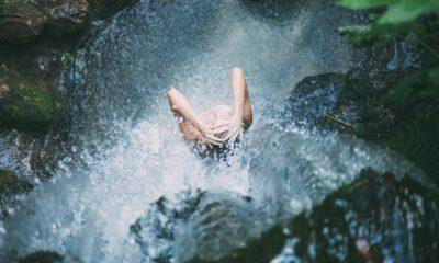 Zdjęcie ilustracyjne, kobieta pod wodospadem